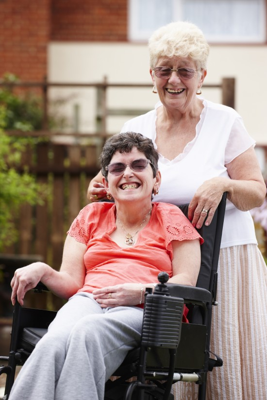 disabled woman with carer in garden