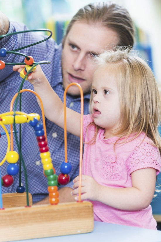 Man and his special needs daughter playing with toy